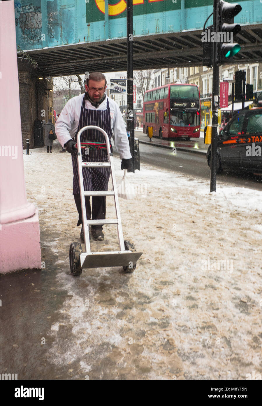 trader pushing barrow through snow camden market - Stock Image