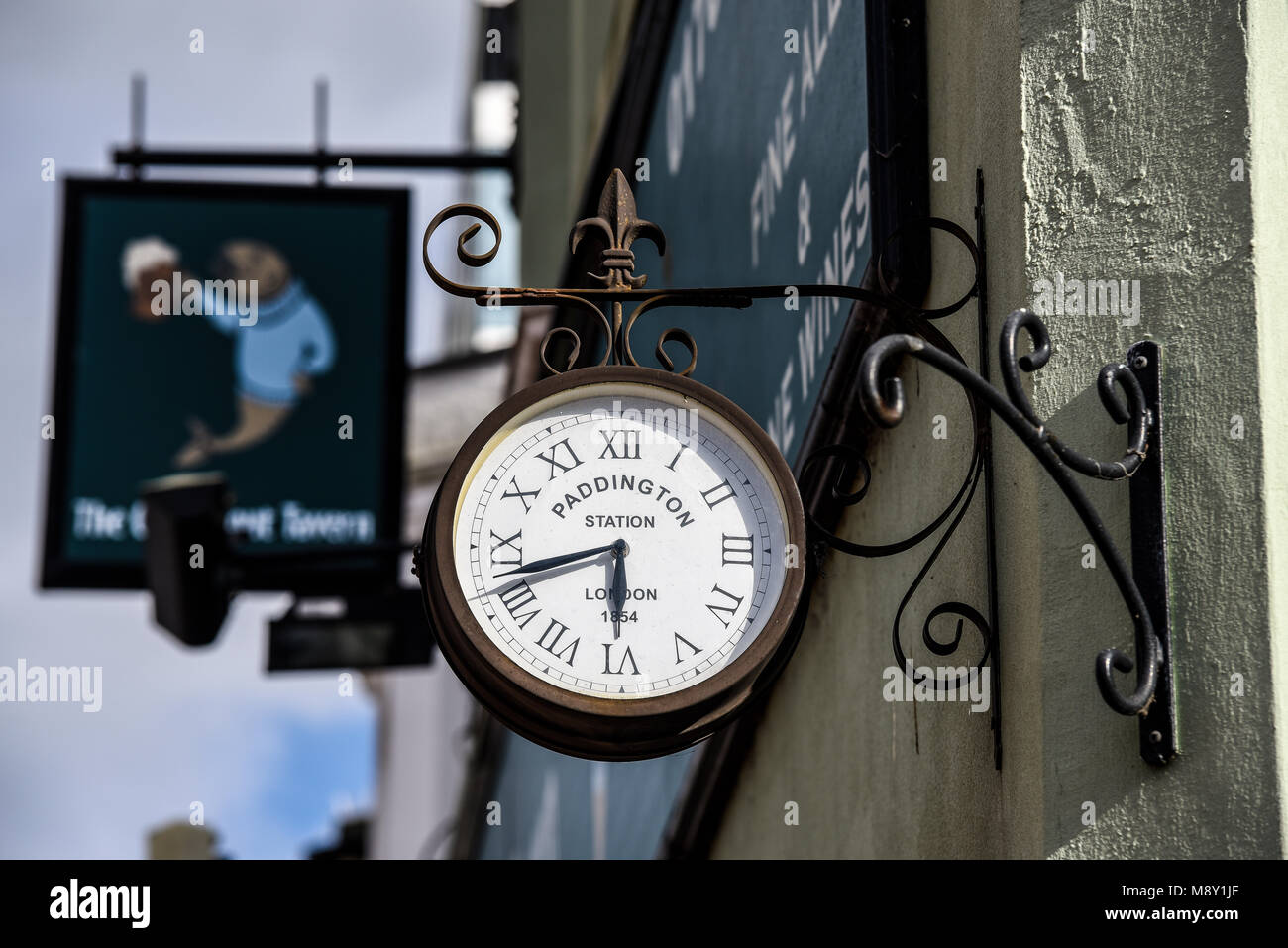Small copy of Paddington railway station clock on the wall of a pub. External wall mounted - Stock Image