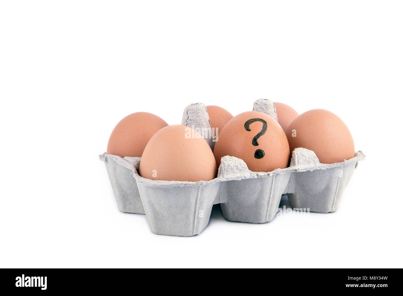Close-up view of raw chicken eggs with question mark in box on white background - Stock Image