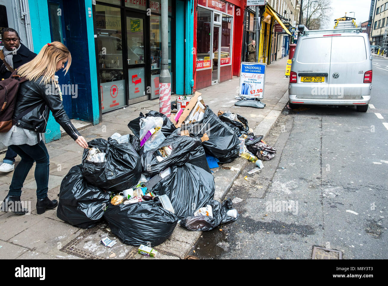 A pile of refuse black bags piled up on a pavement in Lambeth London. - Stock Image