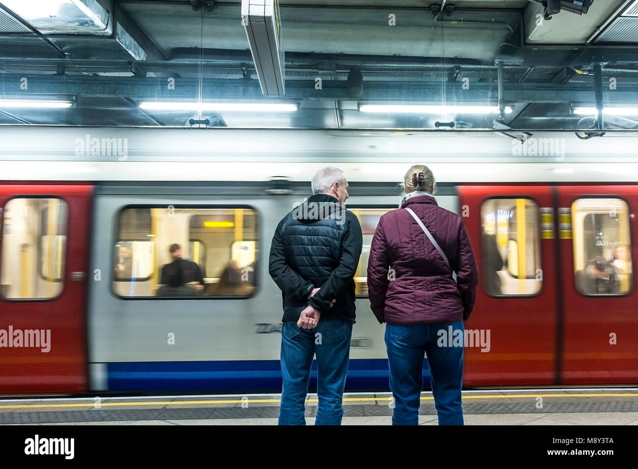 People waiting on a platform as their tube train arrives. - Stock Image