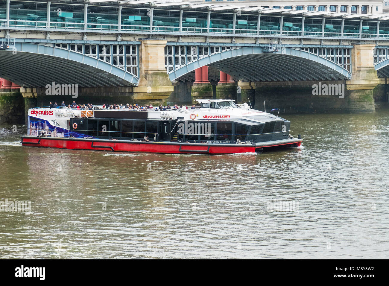 The Millenium Diamond, flagship of City Cruises passes under Blackfriars Bridge on the River Thames in London. - Stock Image