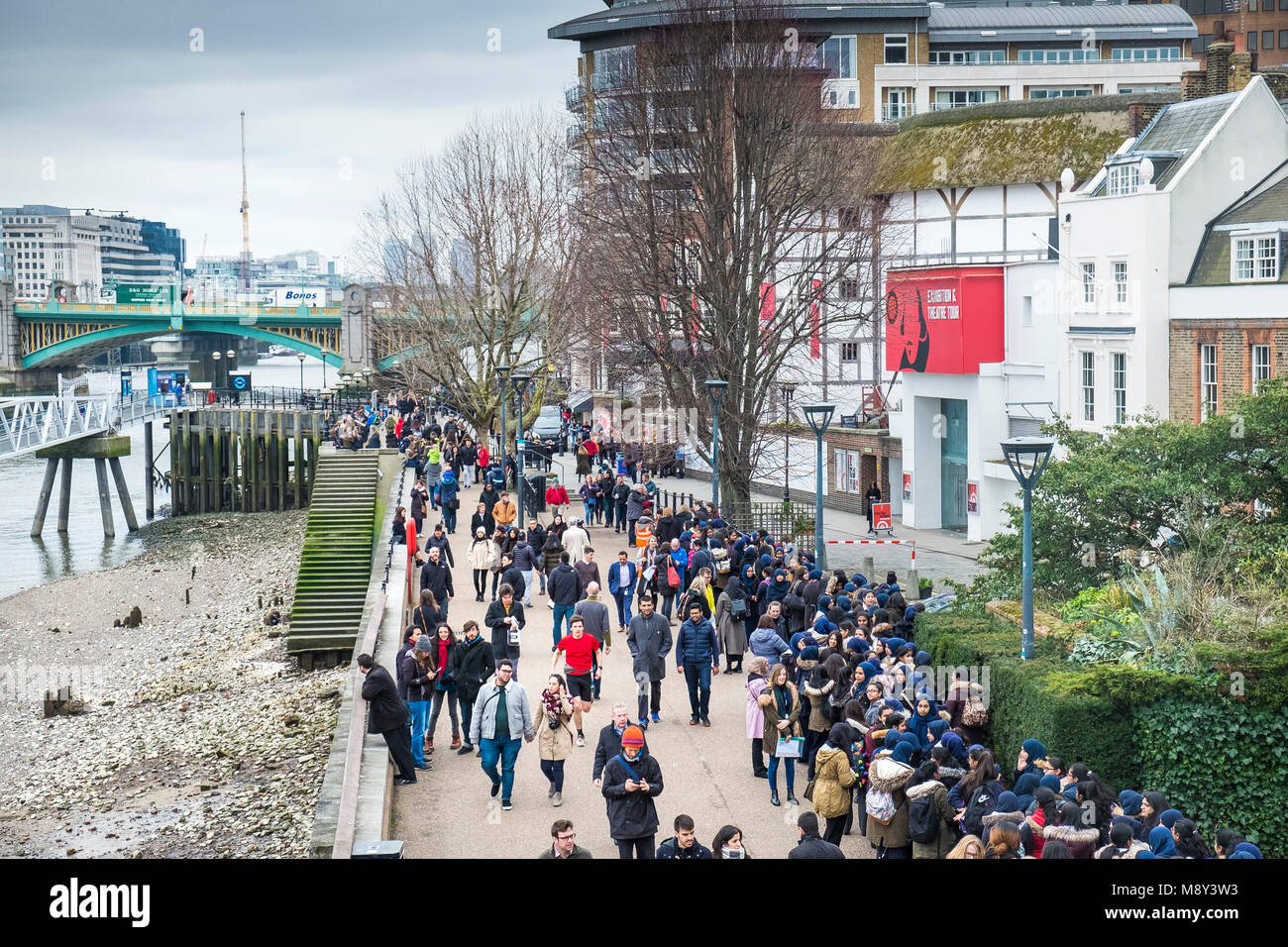 People walking, standing and waiting outside the Globe Theatre on the South Bank in London. - Stock Image