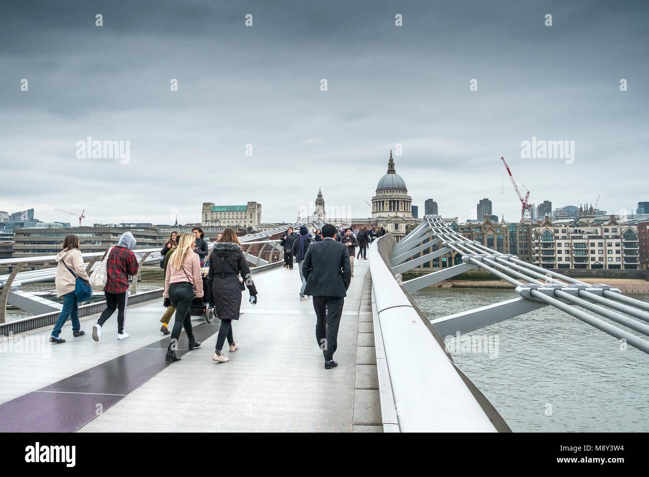 Pedestrians crossing the Millenium Bridge in London on a cold overcast day. Stock Photo