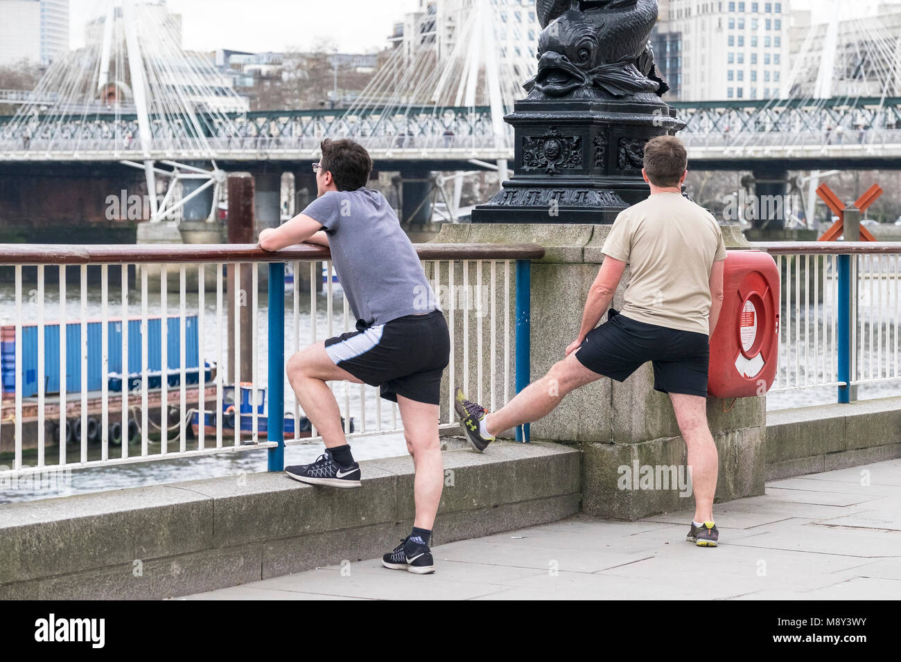 Runners stretching before a run on the Southbank in London. - Stock Image