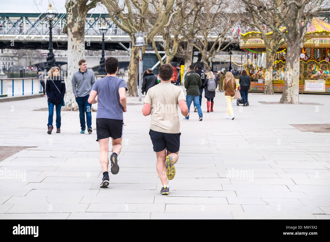 Two runners on the Southbank in London. - Stock Image