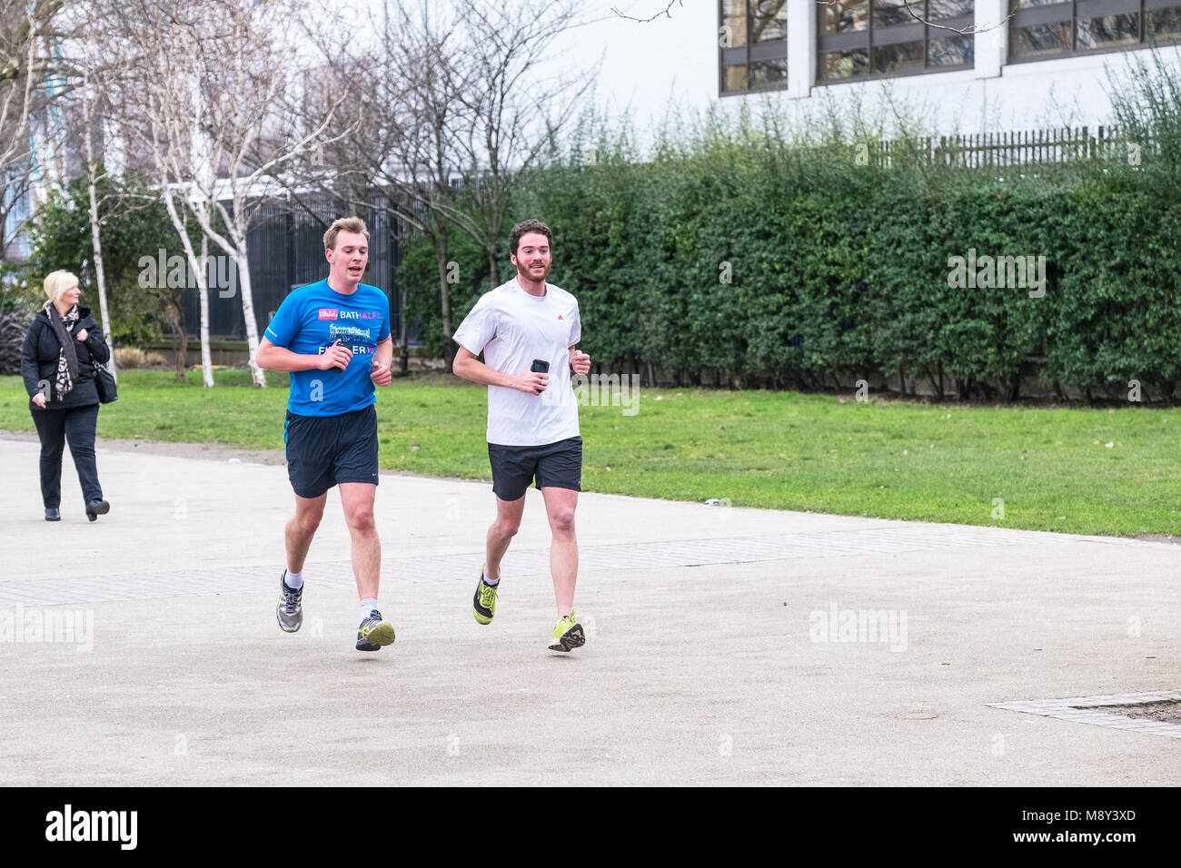 Two runners on the South Bank in London. - Stock Image