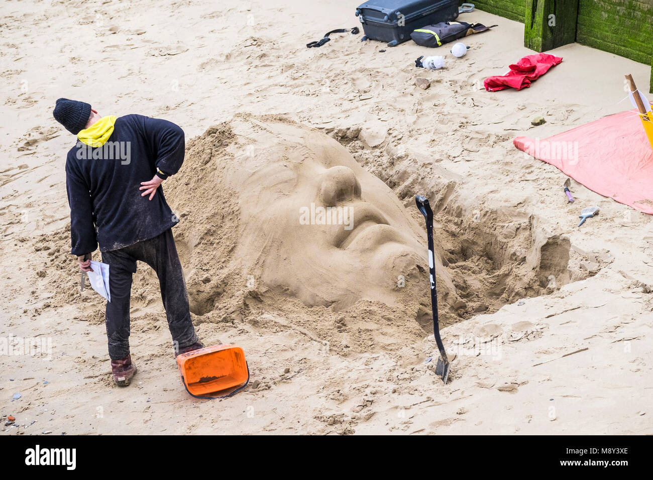 A sculptor creating a sand sculpture on the foreshore of the River Thames on the South Bank in London. - Stock Image