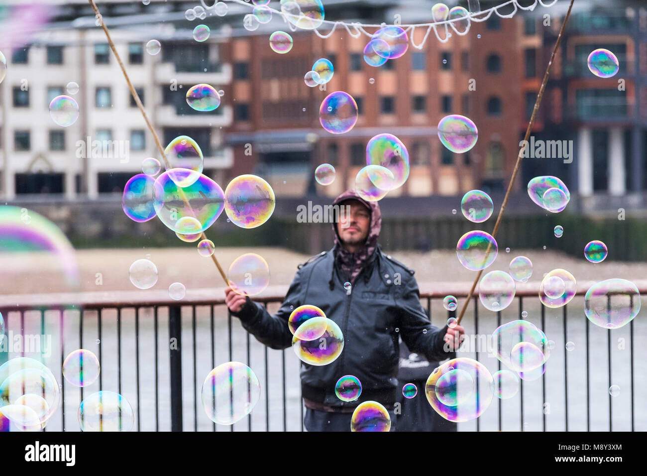 A man creating colourful bubbles on the South Bank in London. - Stock Image