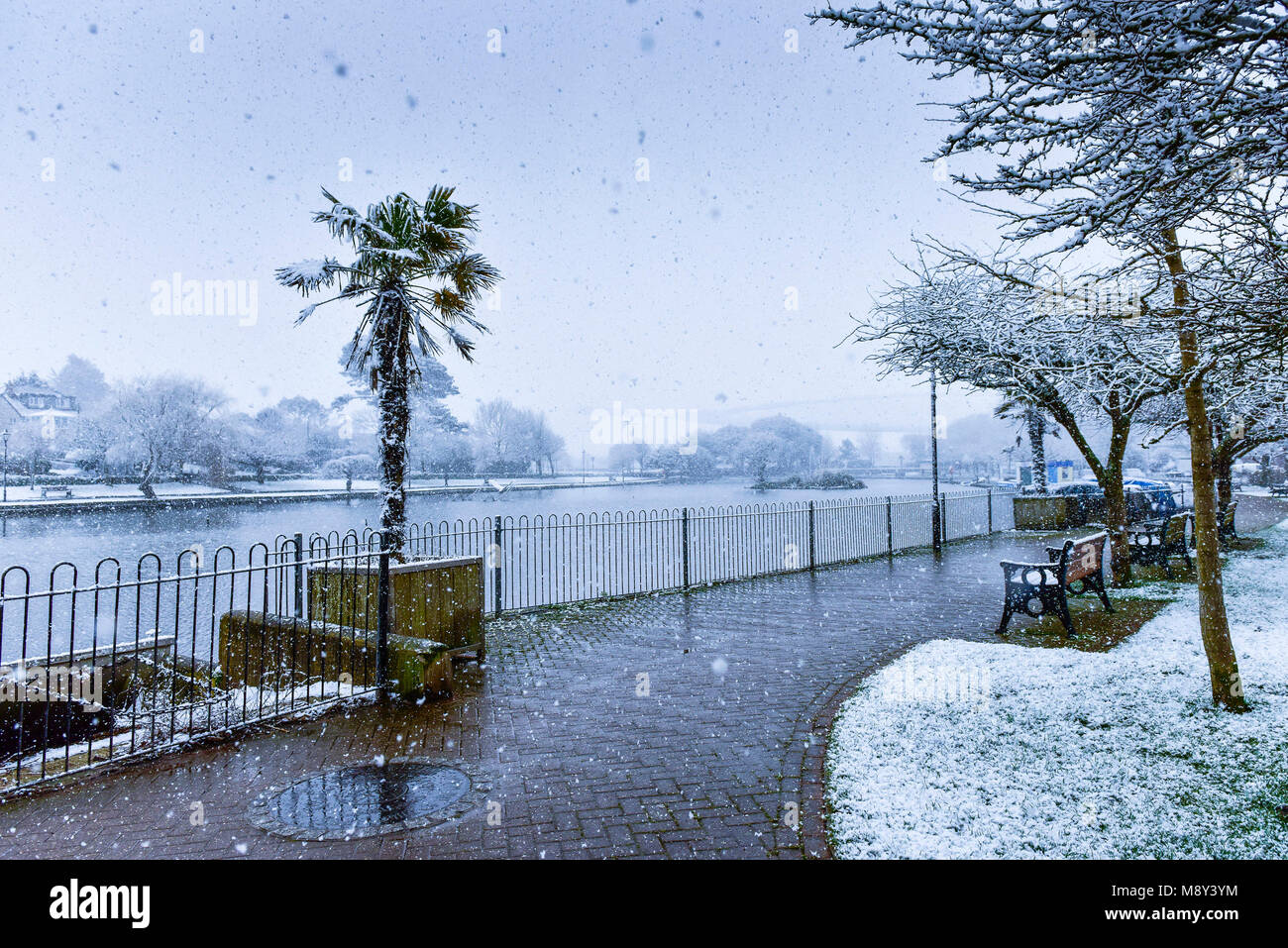 Unusal weather conditions in Cornwall with snow falling over Trenance Boating Lake in Newquay Cornwall. - Stock Image