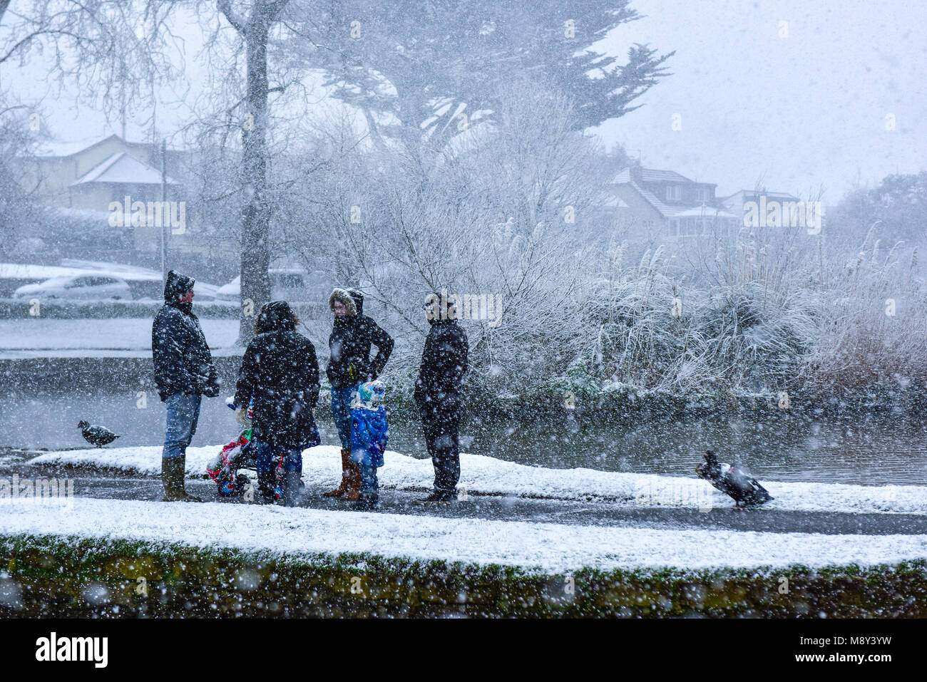 A family standing and talking during a heavy snowfall in Newquay Cornwall. - Stock Image