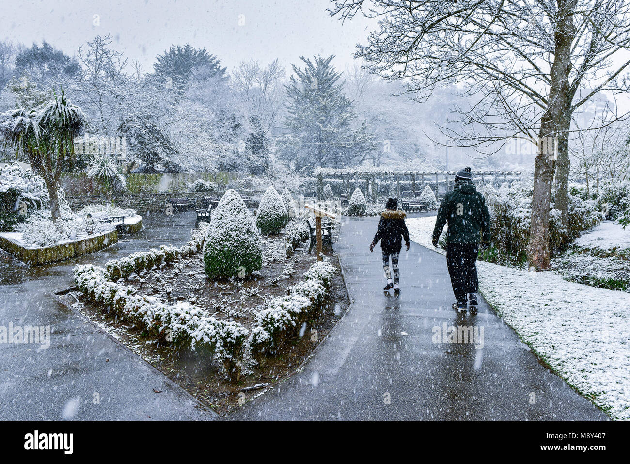 People walking through a heavy snowfall in Trenance Park in Newquay Cornwall. - Stock Image