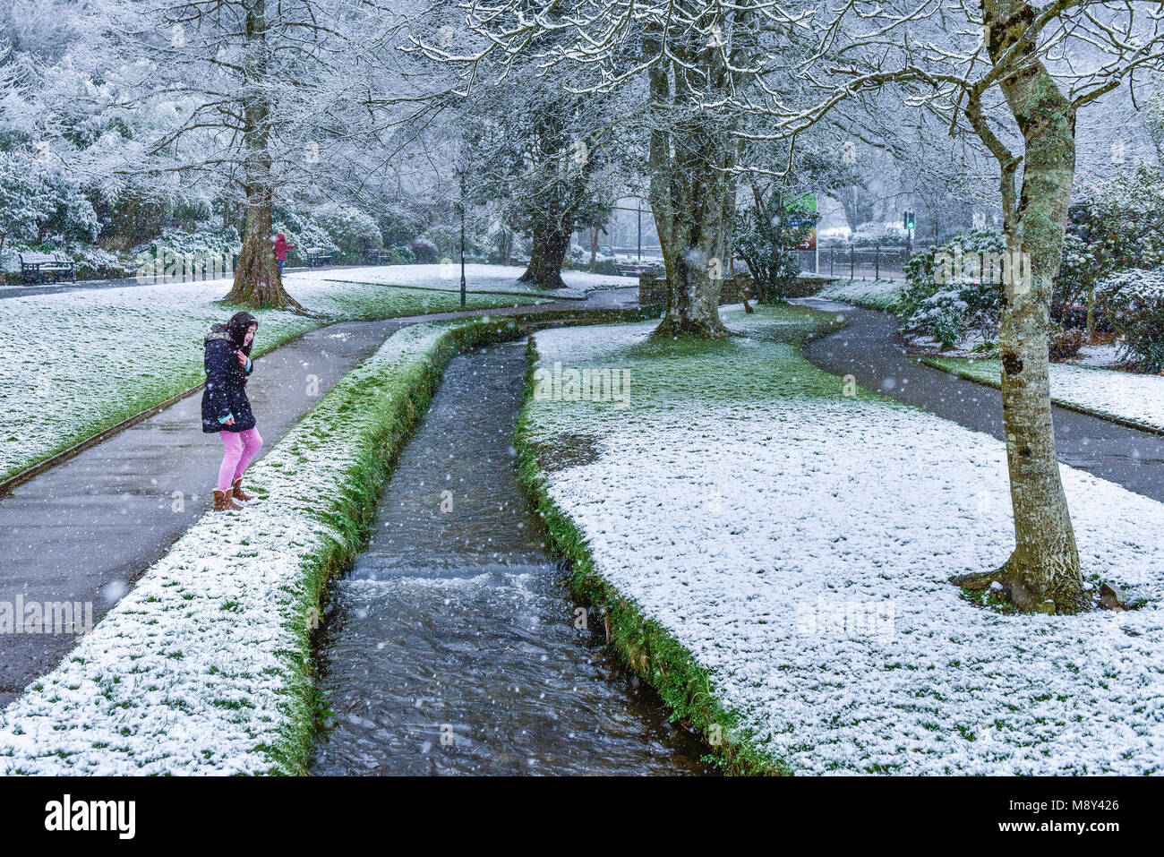 A young girl enjoying the heavy snowfall in Trenance Gardens Newquay Cornwall. - Stock Image