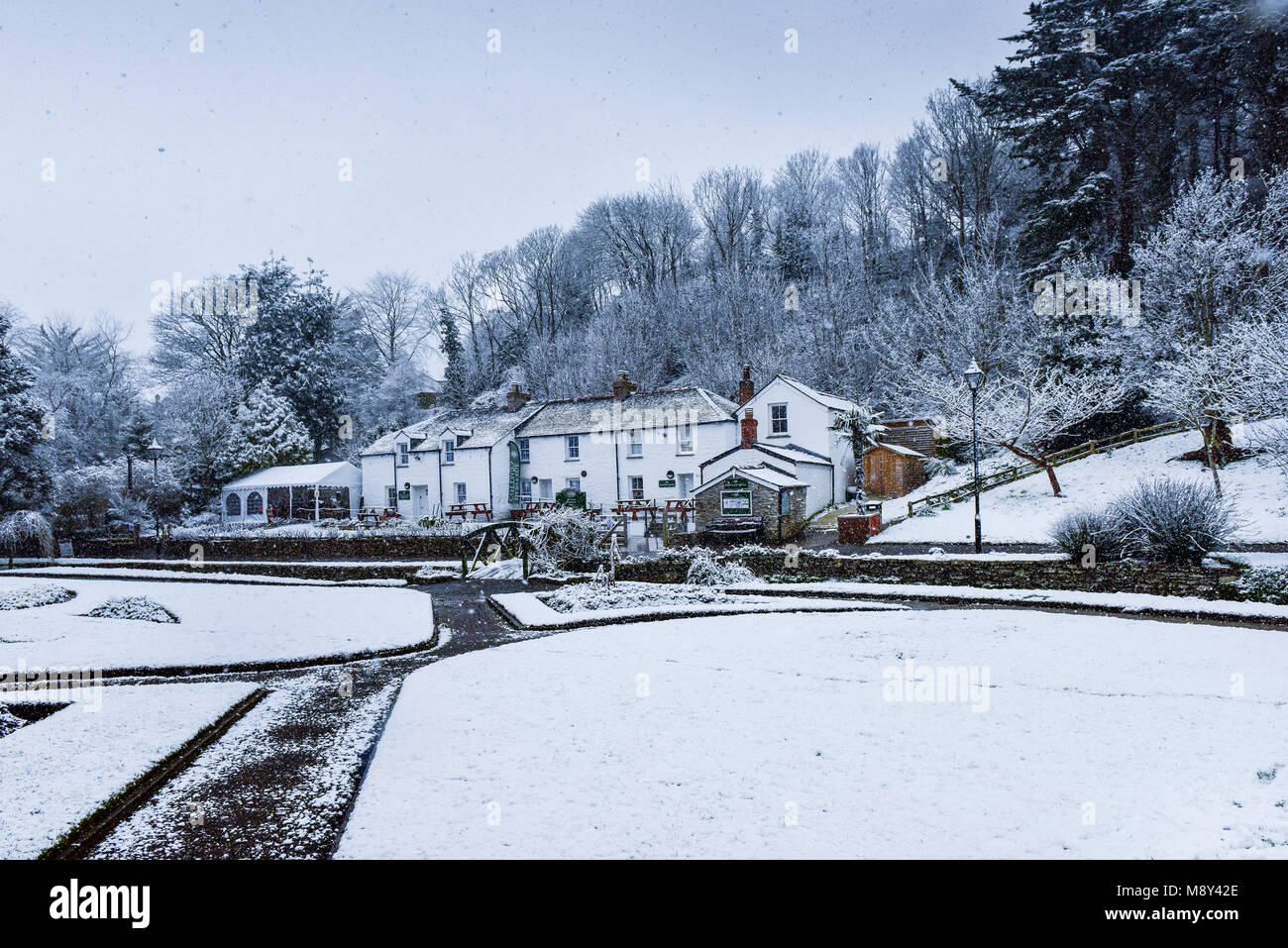Snow falling over the historic Trenance Heritage Cottages in Newquay Cornwall. - Stock Image