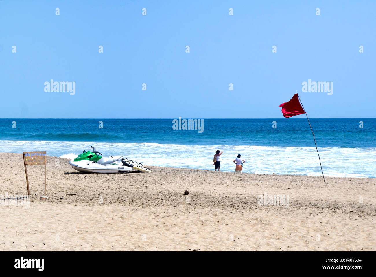 green & white Yamaha WaveRunner beached like some Jules Verne sea creature near 2 women gazing out to sea while - Stock Image