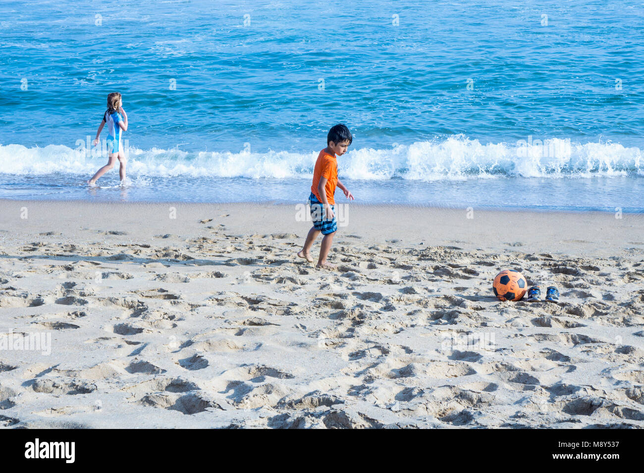 small Caucasian visitors boy & girl play independently near the ocean on  sandy beach in San Agustinillo small - Stock Image