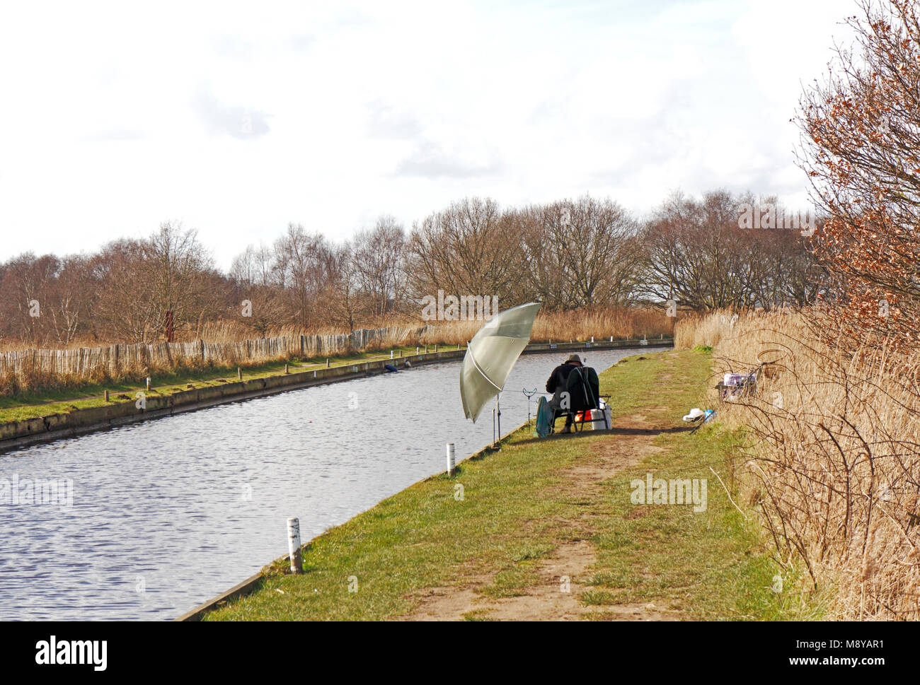 A view of Horsey Dyke with footpath and angler on the Norfolk Broads at Horsey, Norfolk, England, United Kingdom, Stock Photo