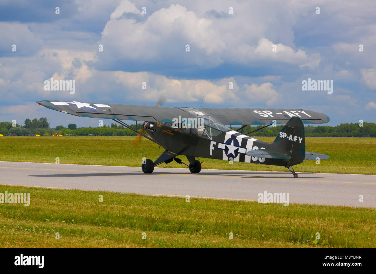 The Piper J-3 Cub (L-4 Grasshopper; military markings) on runway during International Air Show at the 90th Jubilee - Stock Image