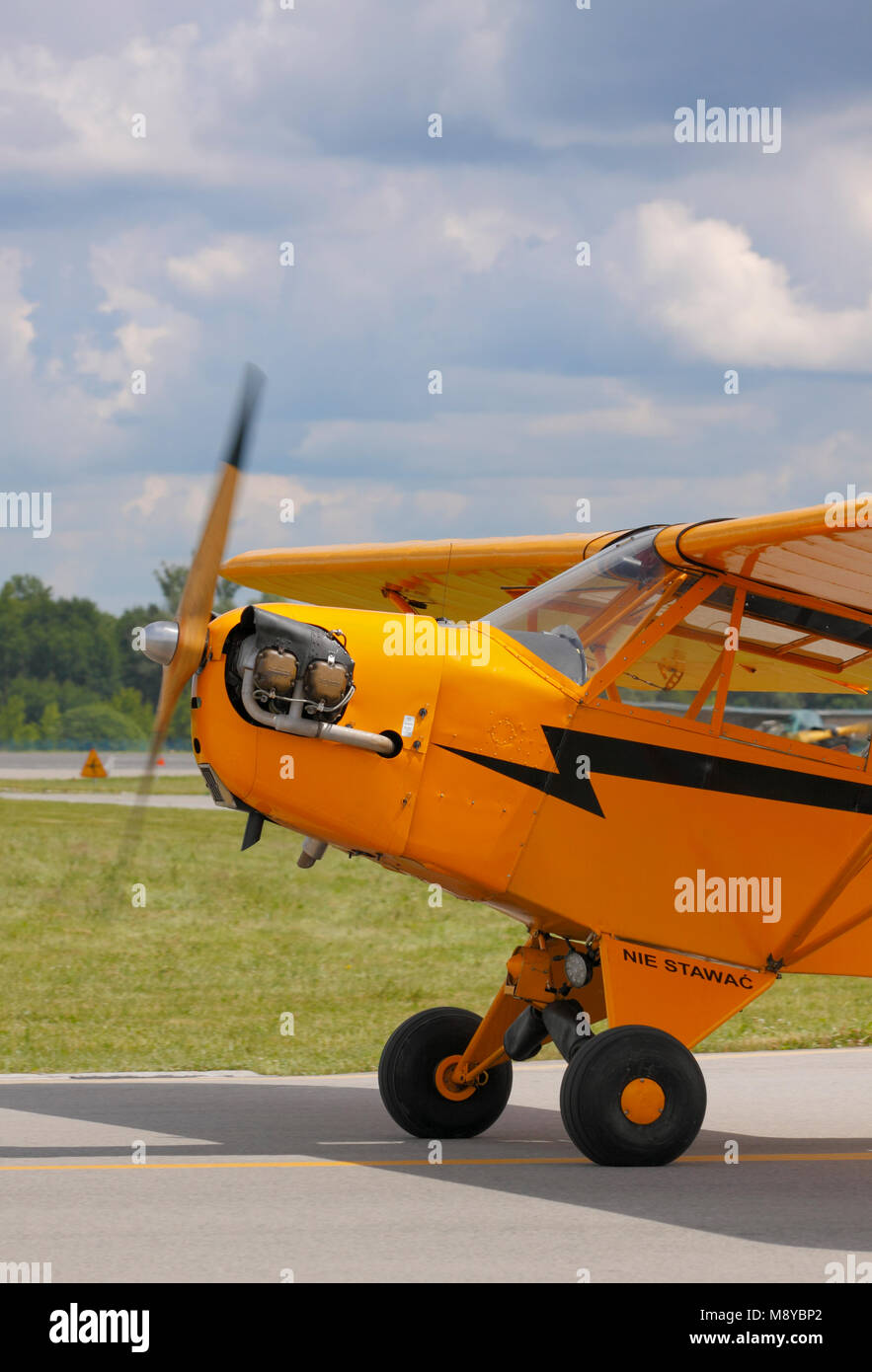 The Piper J-3 Cub ('Cub Yellow' hue) on runway during International Air Show at the 90th Jubilee of The - Stock Image