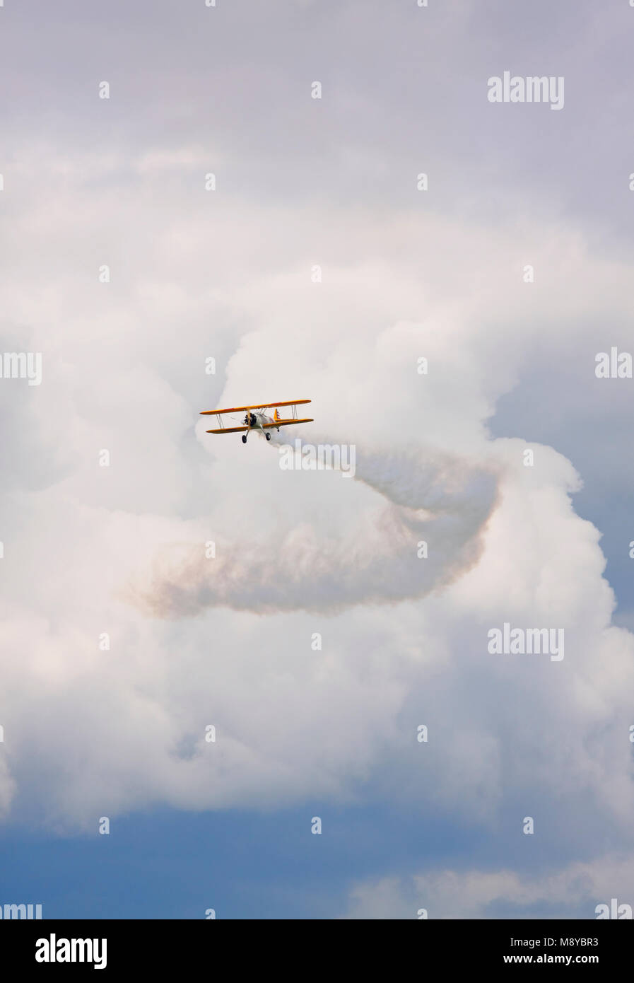 The Boeing Stearman N2S-3 flying over cloudy sky during International Air Show at the 90th Jubilee of The Polish - Stock Image