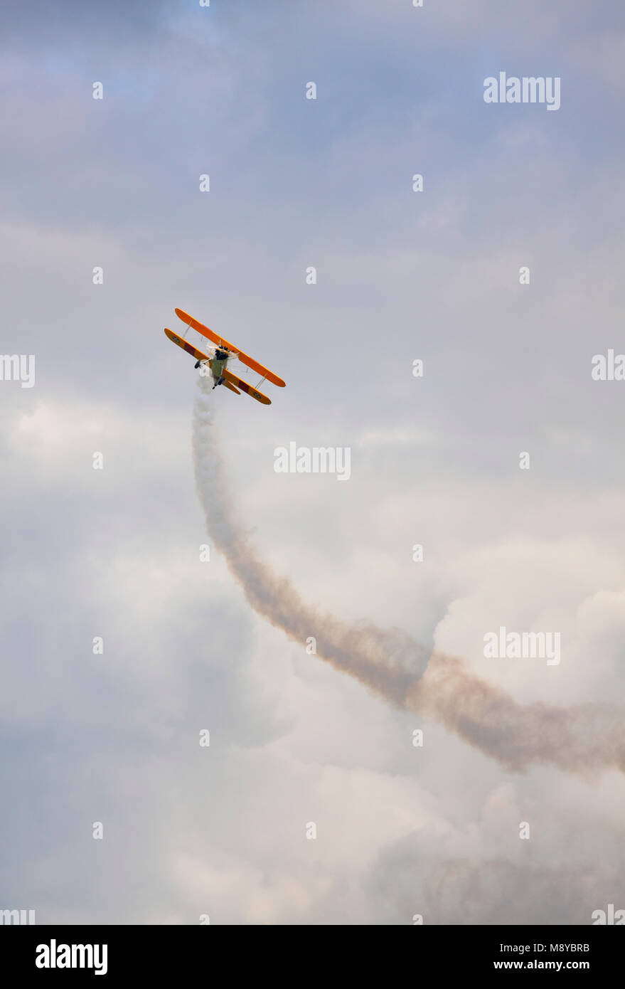 The Boeing Stearman N2S-3 flying up over cloudy sky during International Air Show at the 90th Jubilee of The Polish - Stock Image