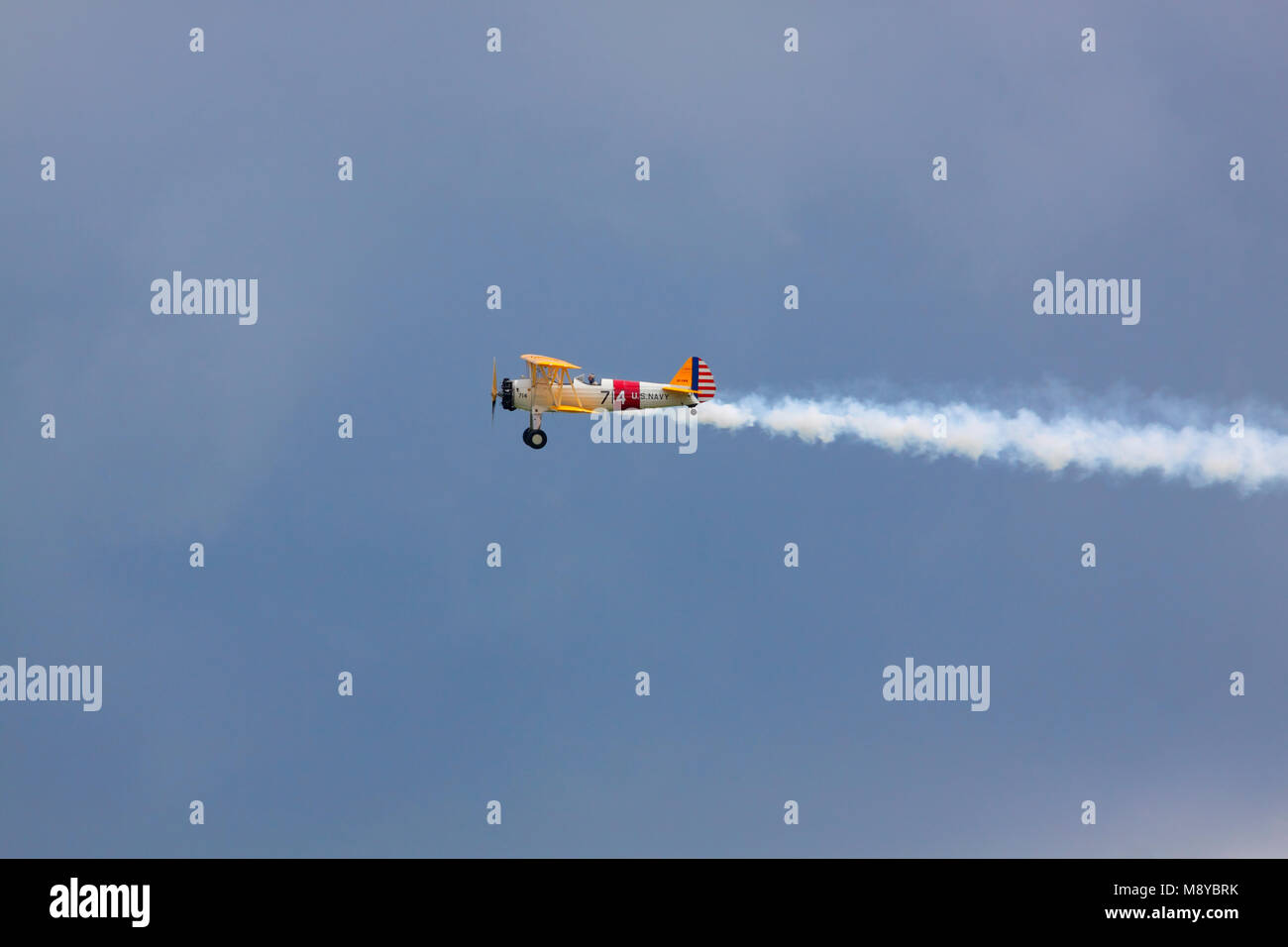 The Boeing Stearman N2S-3 in US Navy markings flying over dark sky during International Air Show at the 90th Jubilee - Stock Image