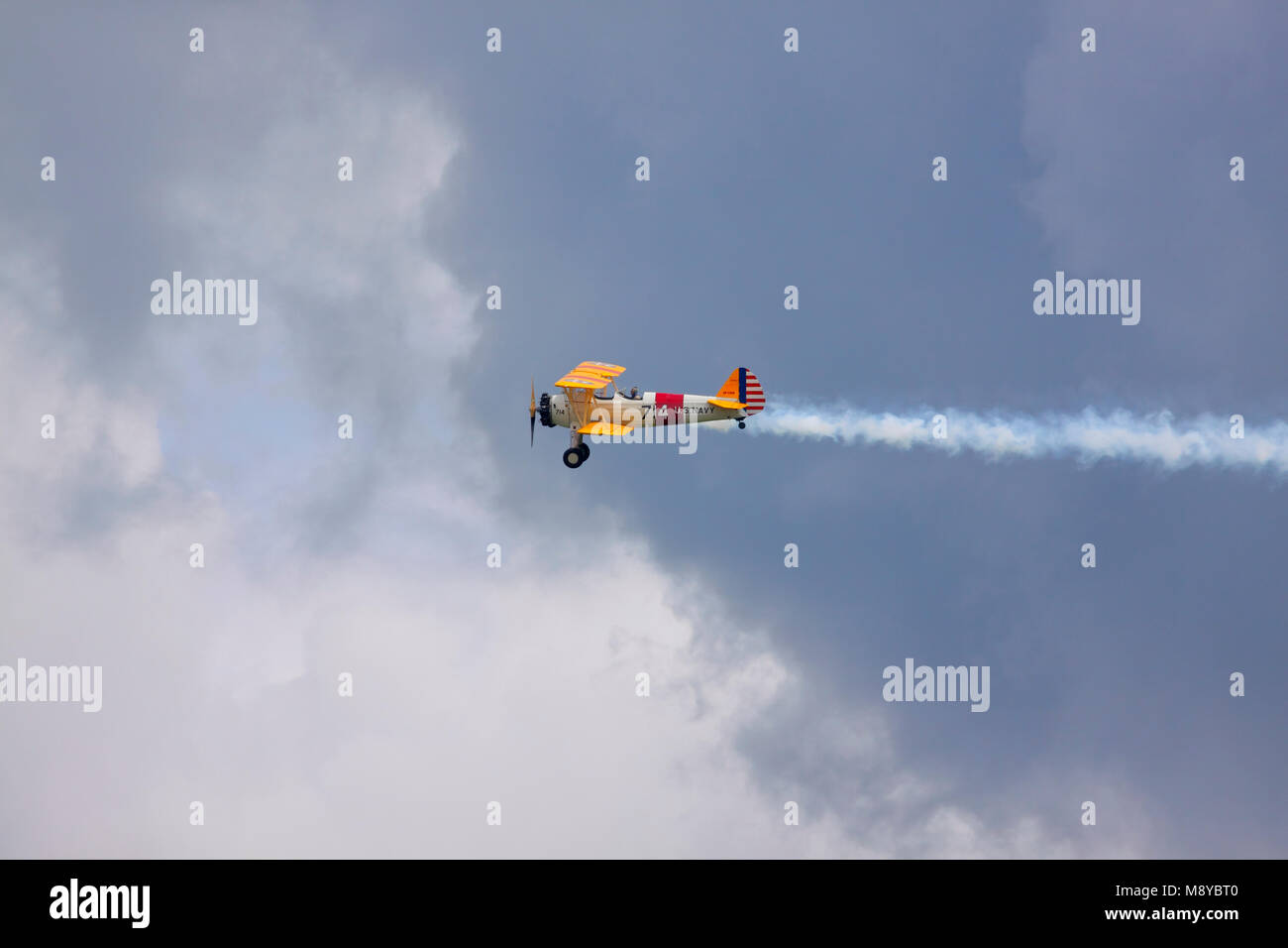 The Boeing Stearman N2S-3 in US Navy markings flying over cloudy sky during International Air Show at the 90th Jubilee - Stock Image