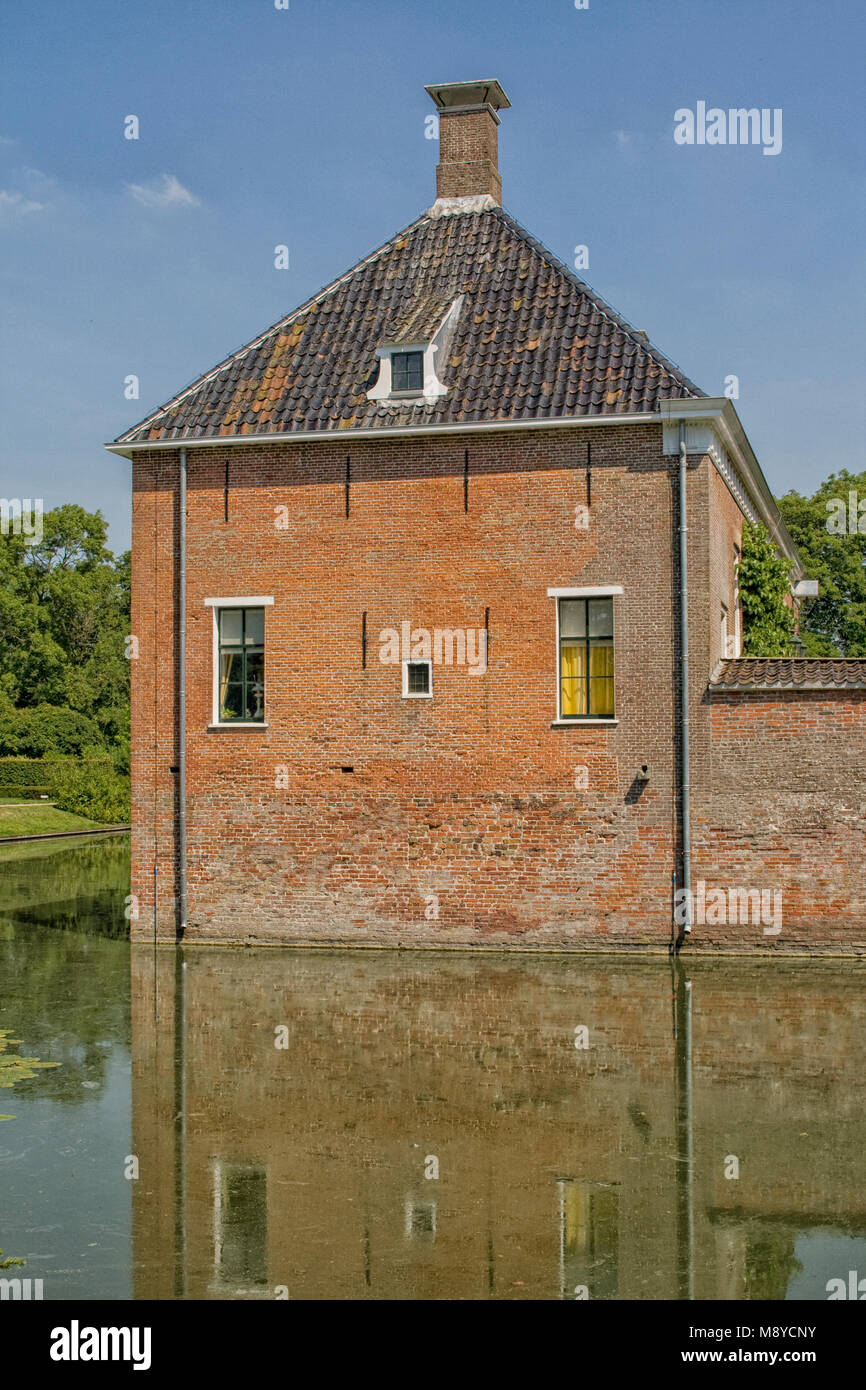 Beautiful old mansion with moat and bridge from 14th century in the north of the Netherlands - Stock Image