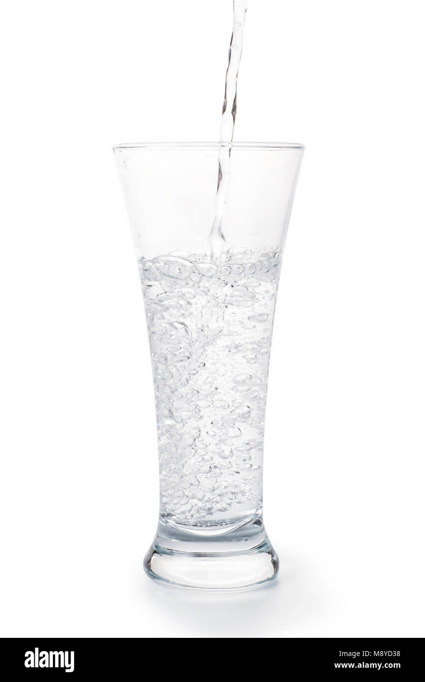 Clear carbonated water with bubbles pours into the glass. Isolated on white, clipping path included - Stock Image