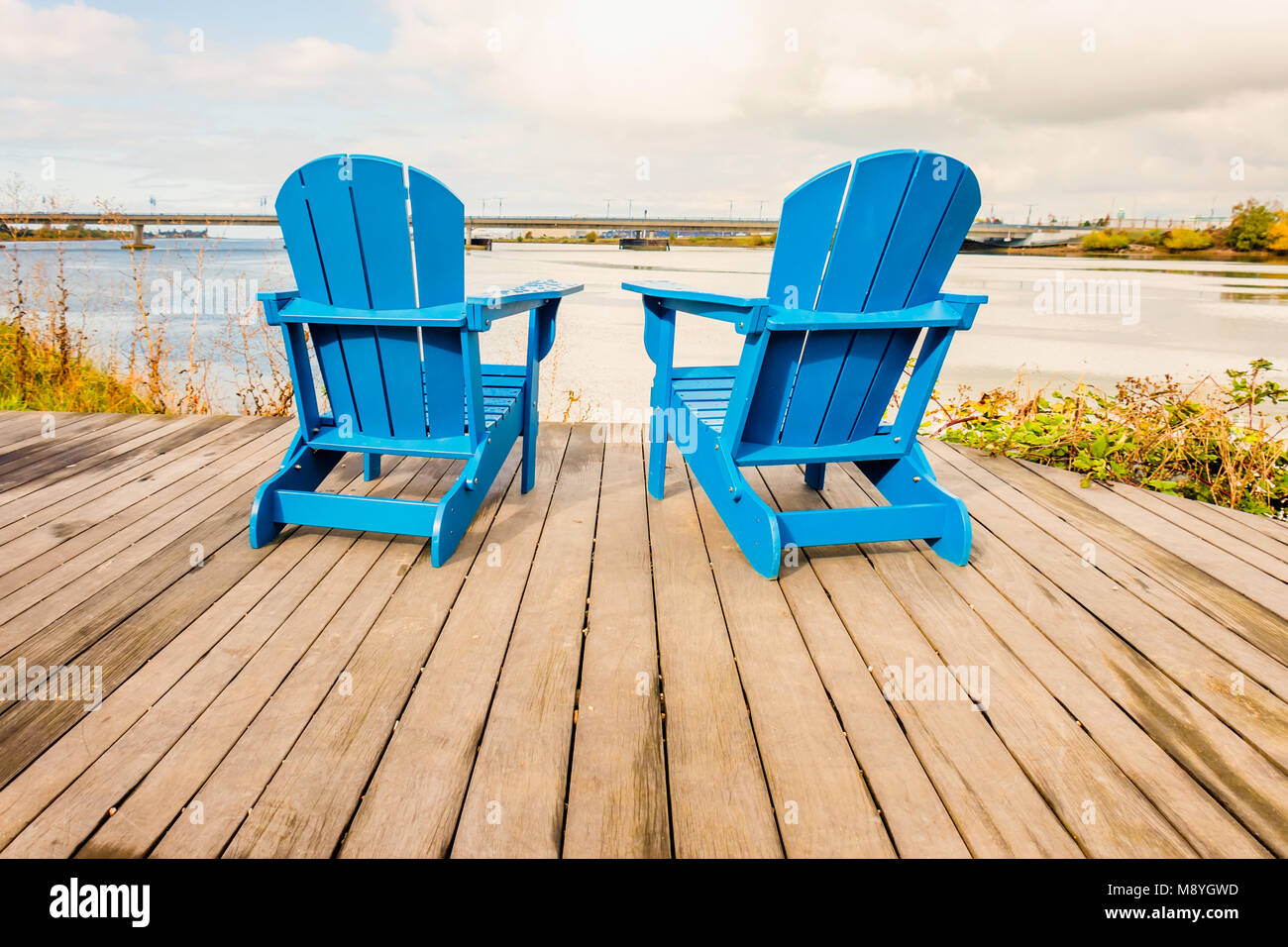 Two Empty Blue Chaise Longue Stand On The Wooden Floor Opposite River And Bridge
