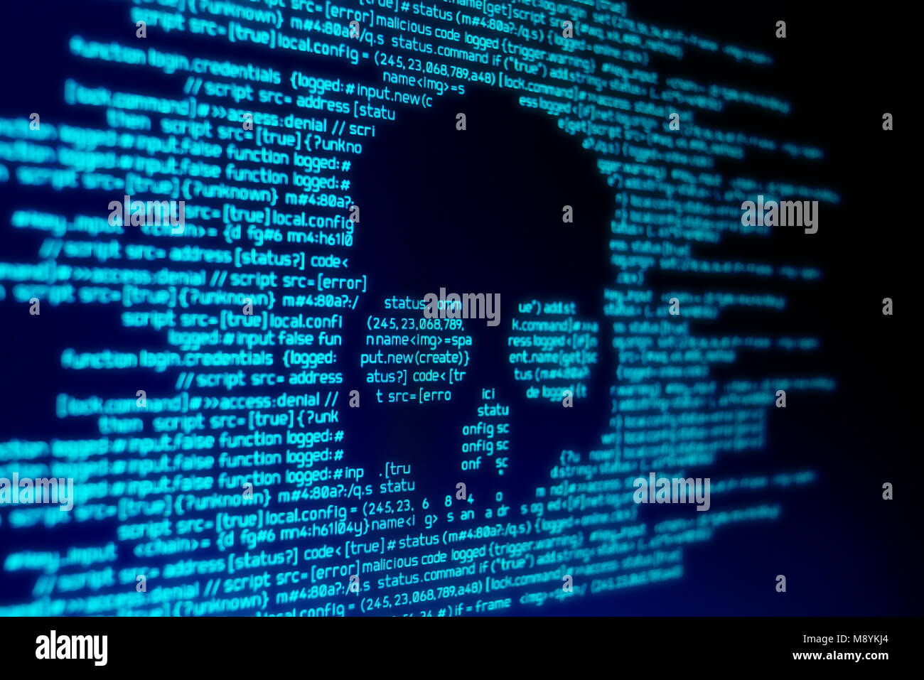 Computer code on a screen with a skull representing a computer virus / malware attack. - Stock Image
