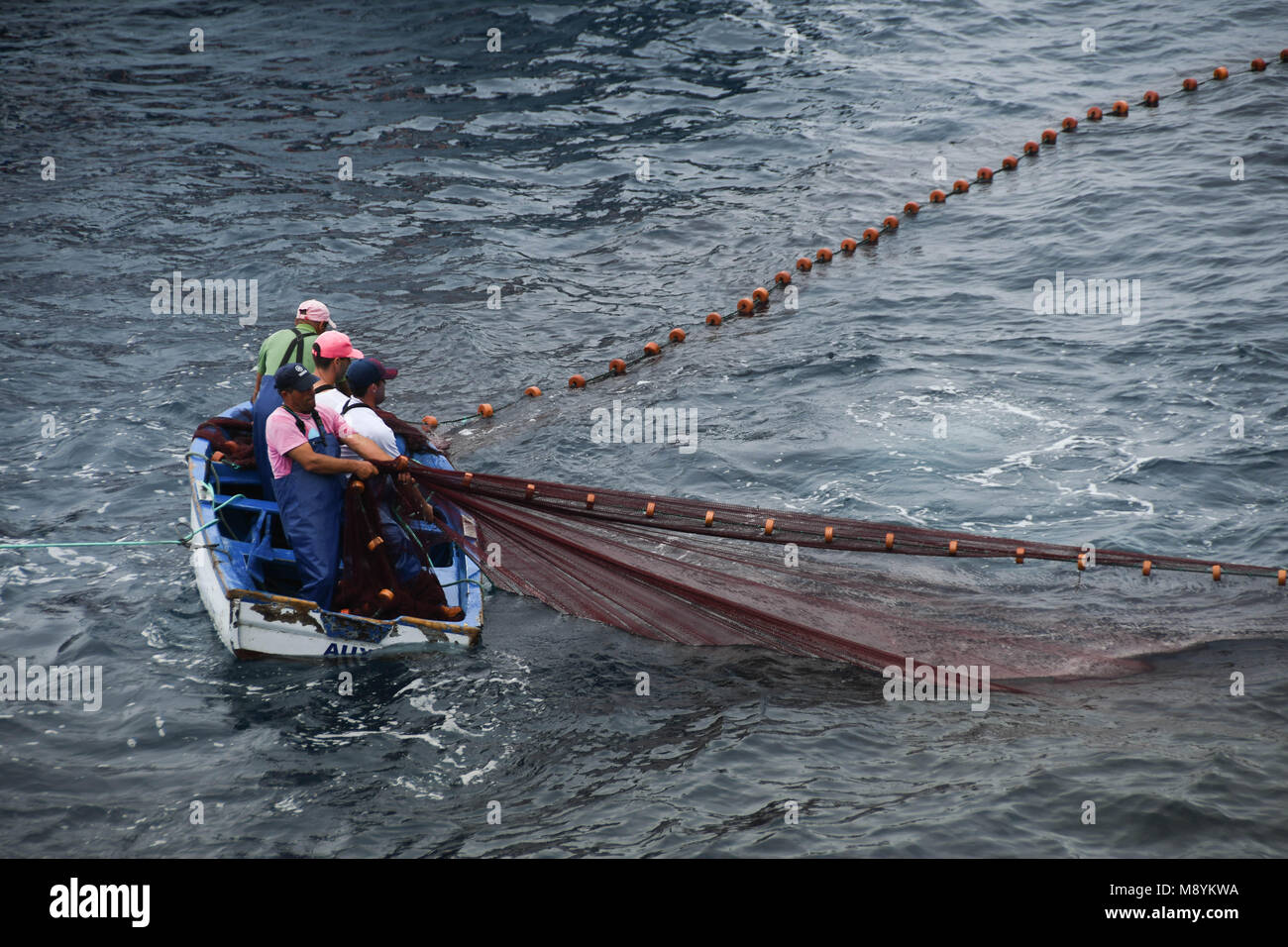 Fisherman in a small boat hauling in their net - Stock Image