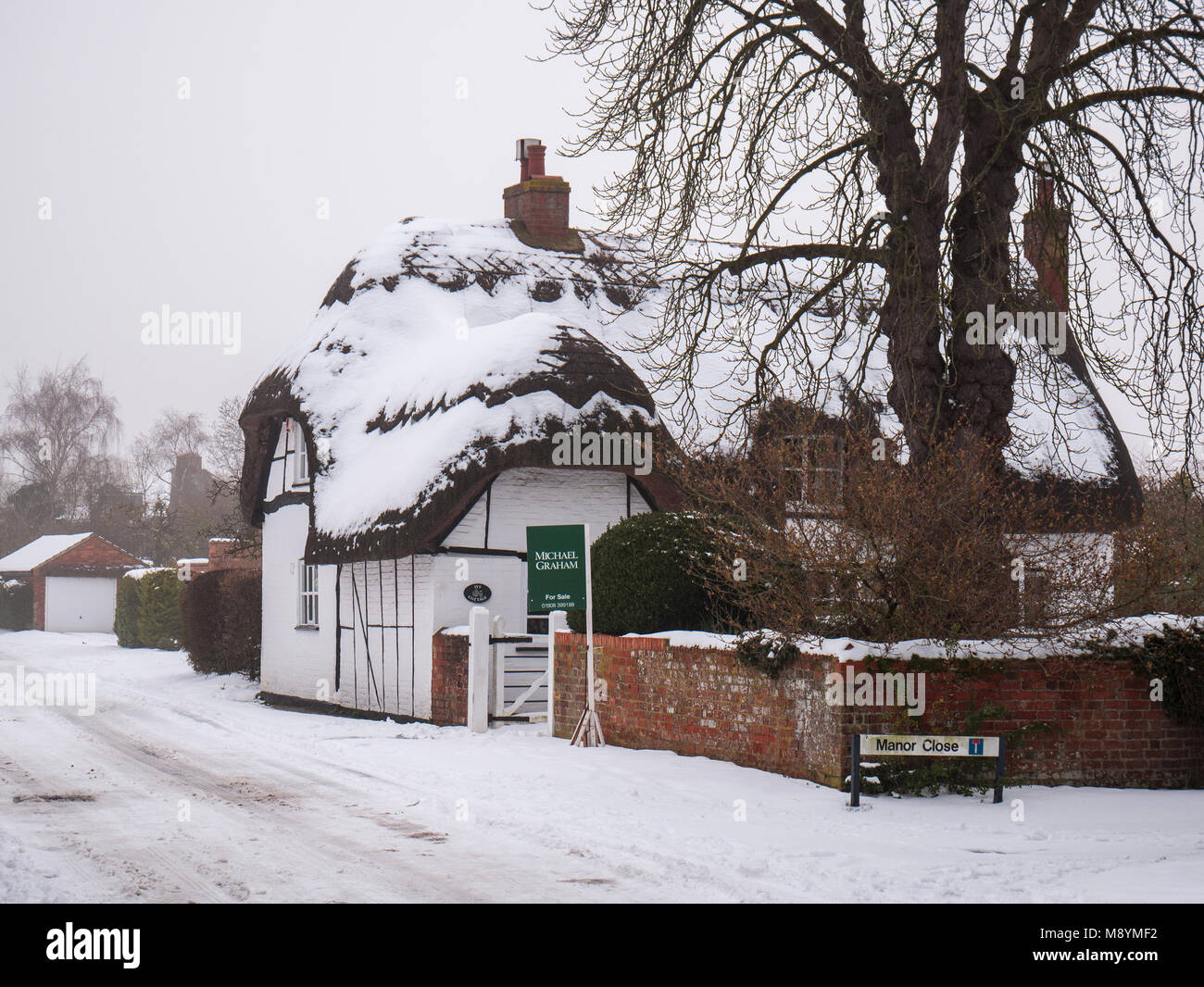 A thatched cottage in the snow, with a for sale sign outside Stock Photo
