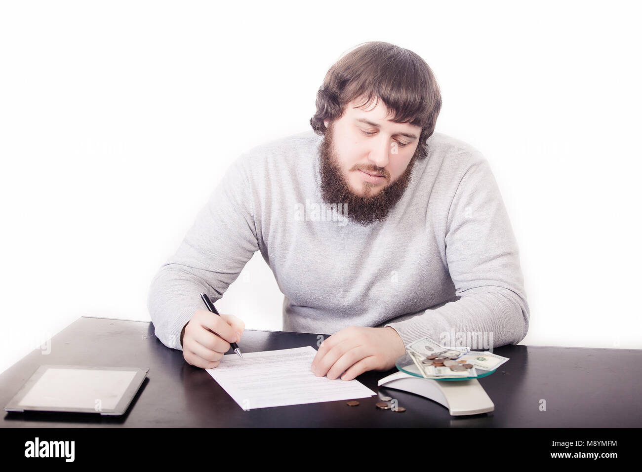 A handsome young programmer, working, dreaming, at the table, looking at the money, coming up with the creation - Stock Image