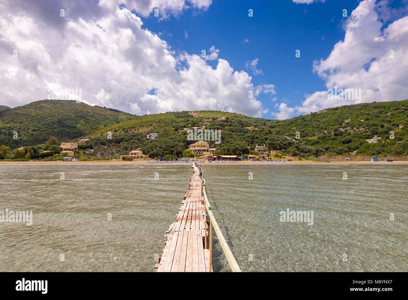 Long wooden pier on Apraos beach near Kassiopi town. Corfu island. Greece. - Stock Image