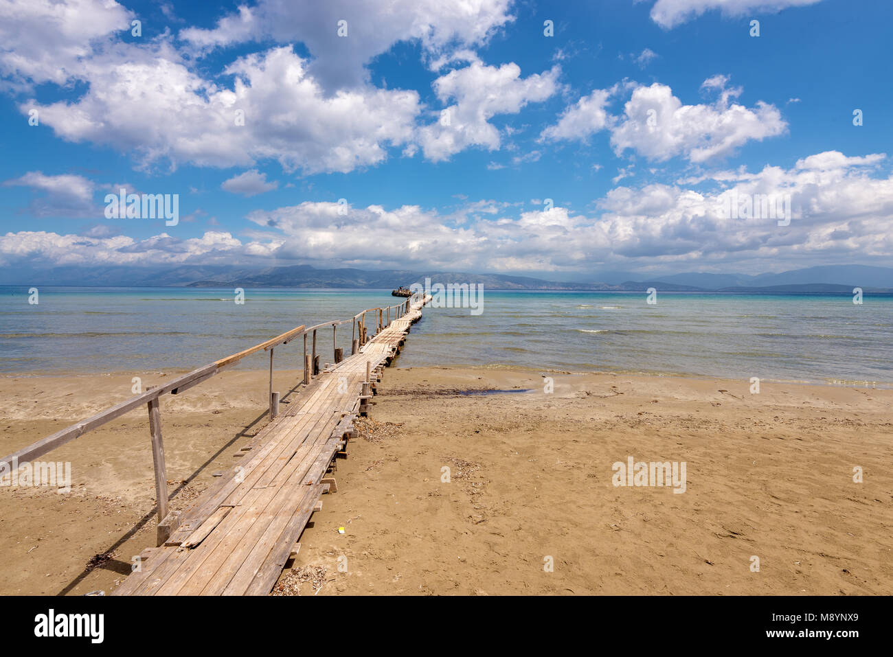 Wooden pier on Apraos beach near Kassiopi town with perfect views of the Albanian mountains. Corfu island. Greece. - Stock Image