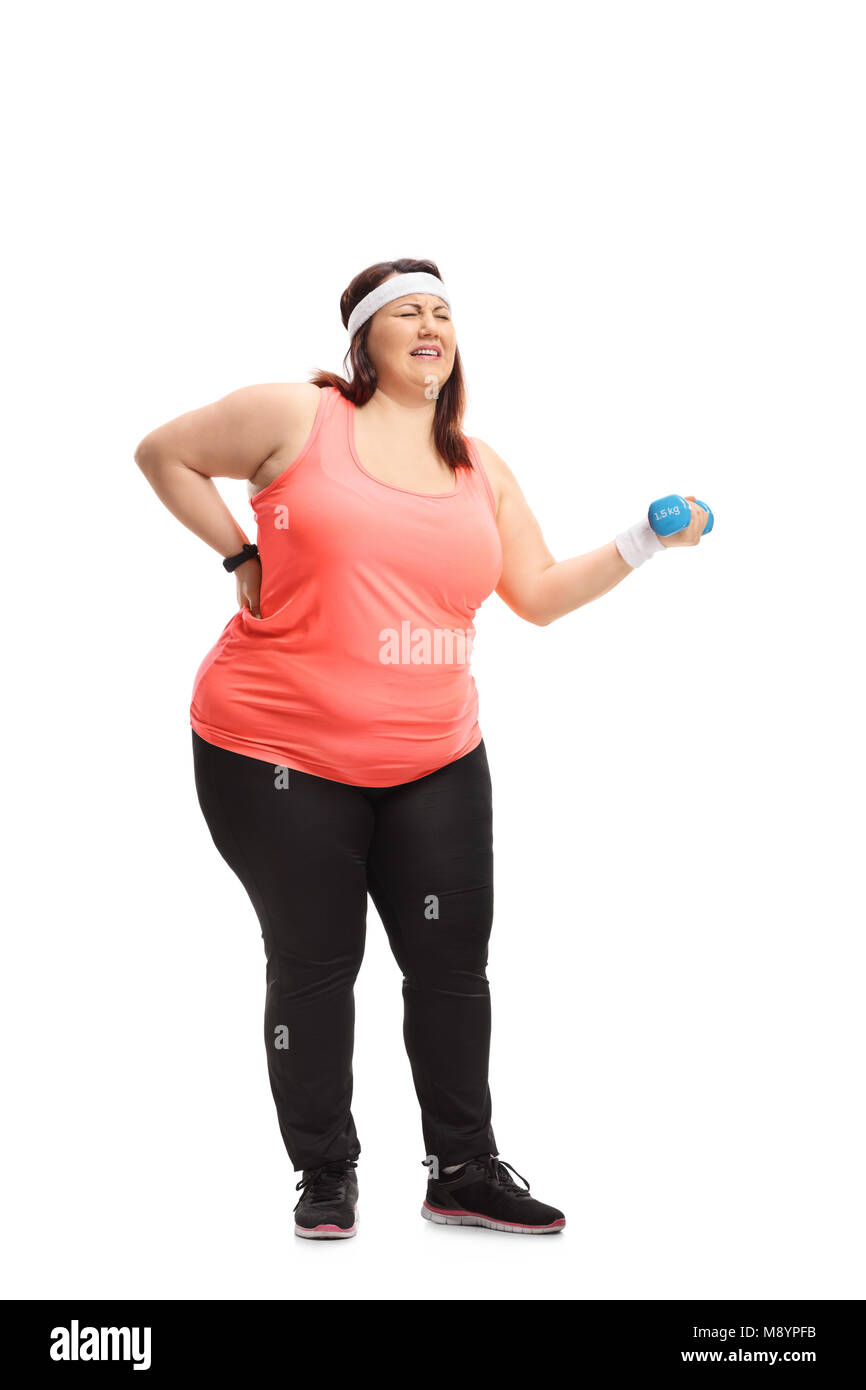 Full length portrait of an overweight woman lifting a small dumbbell and experiencing back pain isolated on white - Stock Image