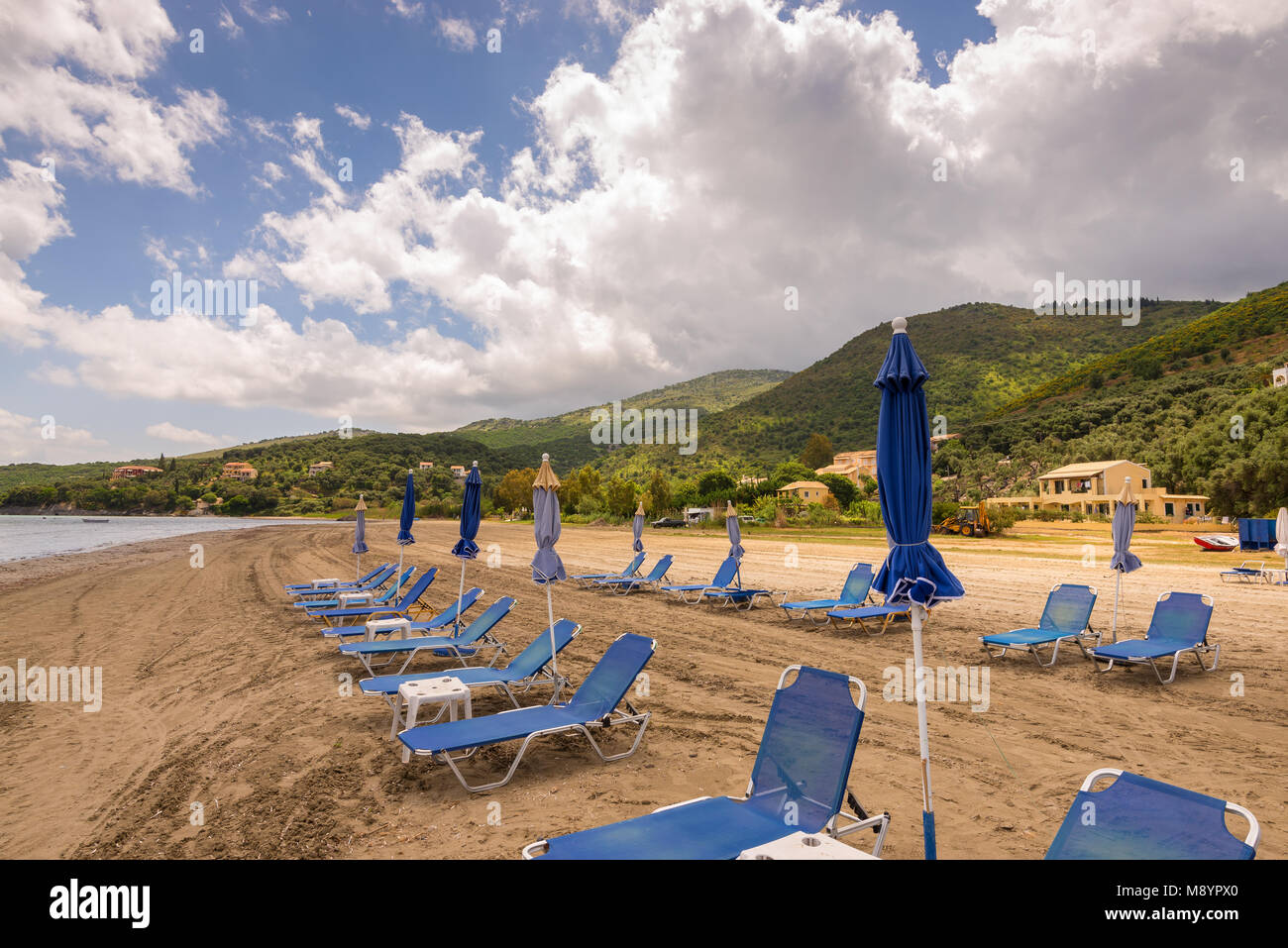 Sunbeds and umbrellas on Kalamaki beach, also now as Apraos beach near Kassiopi on Corfu island. Greece. - Stock Image