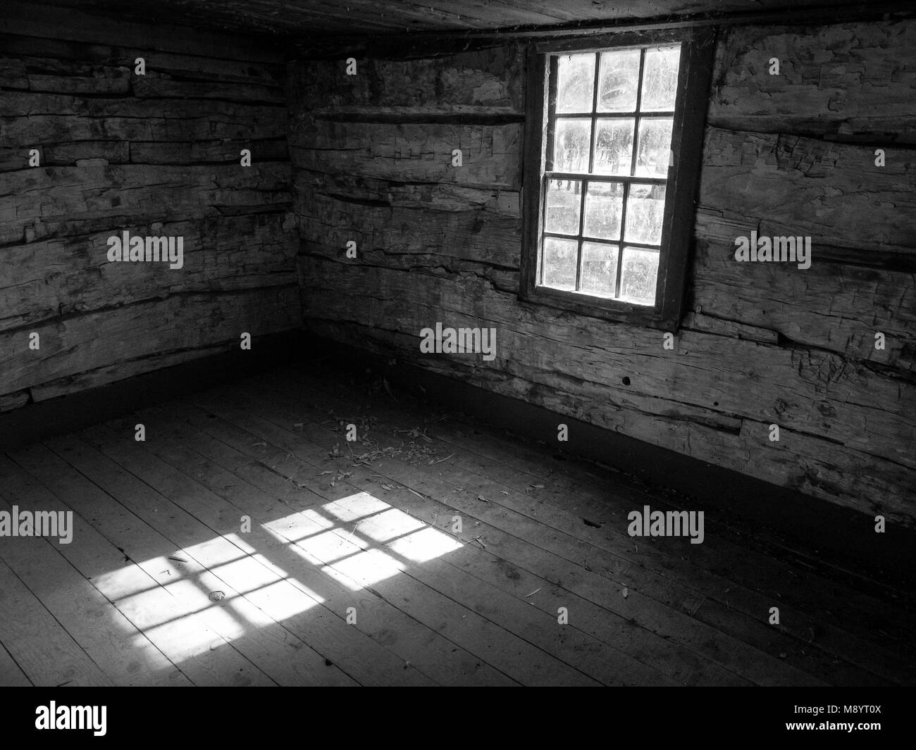 Old Log Cabin Interior, Black and White, Sunlight Through Window - Stock Image
