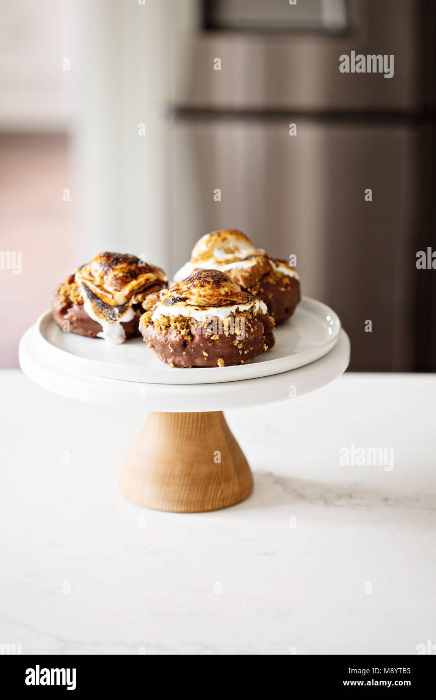 Smores donuts on a cake stand - Stock Image