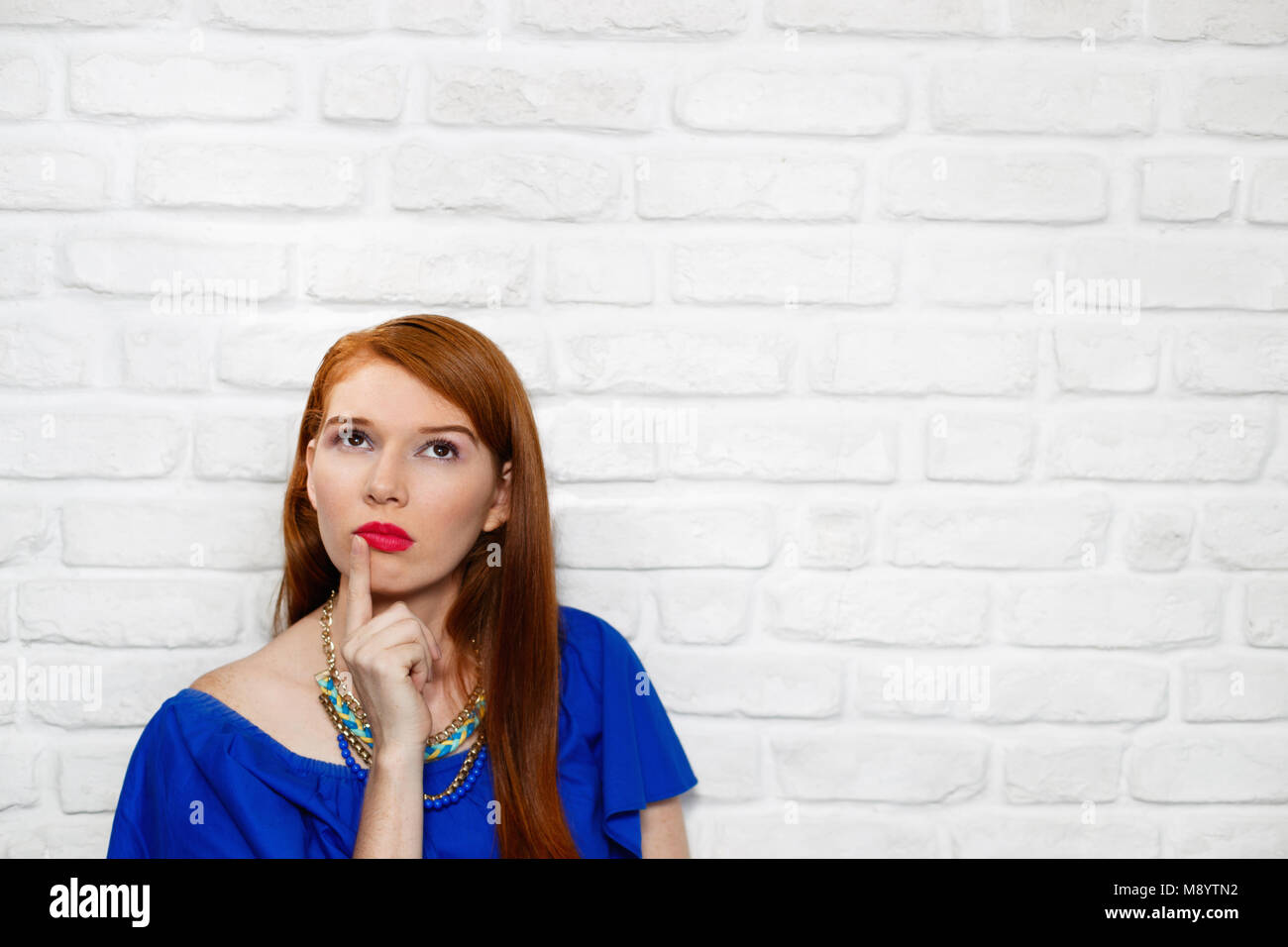 Facial Expressions Of Young Redhead Woman On Brick Wall - Stock Image