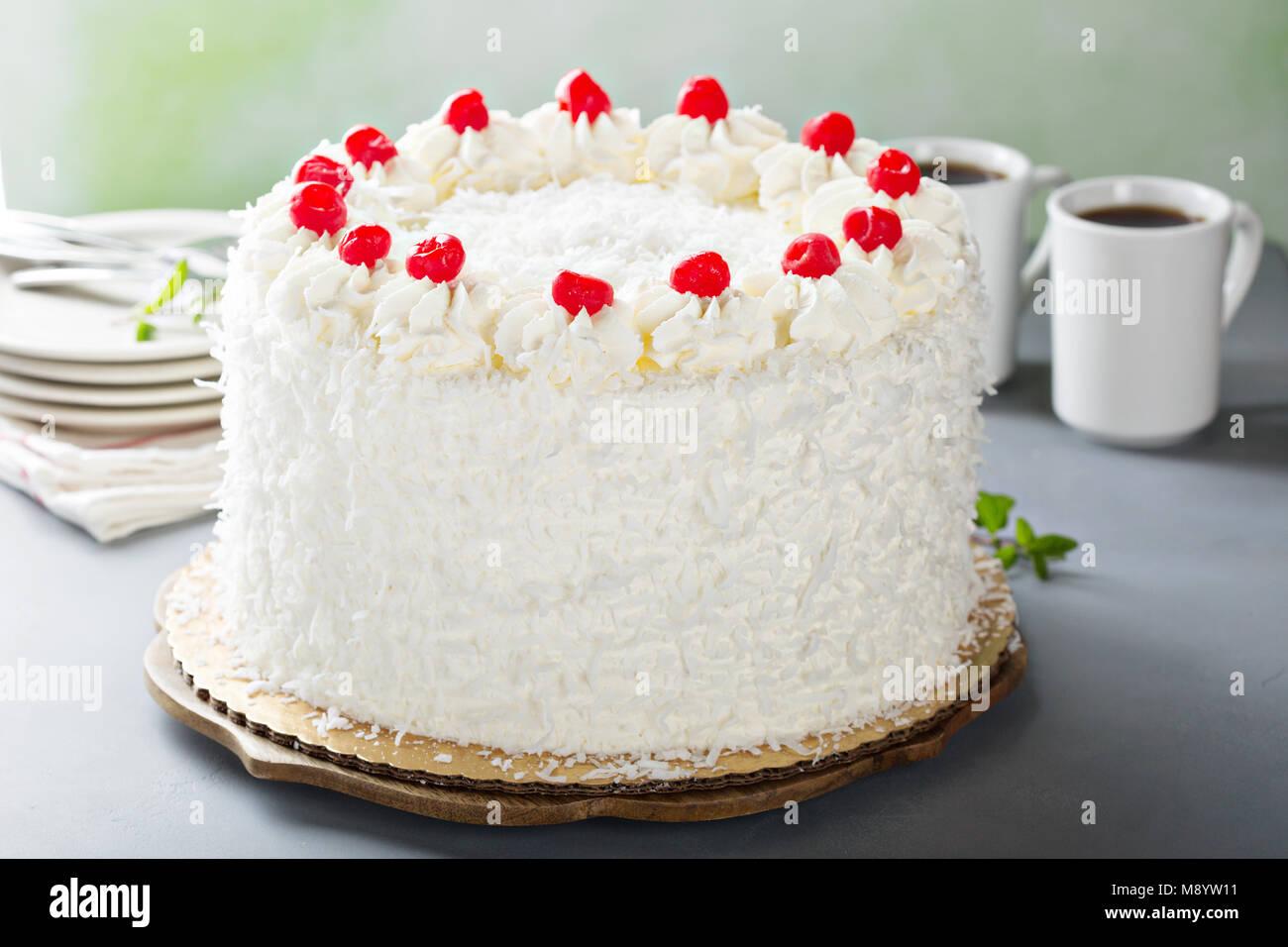 Coconut cake with maraschino cherries - Stock Image