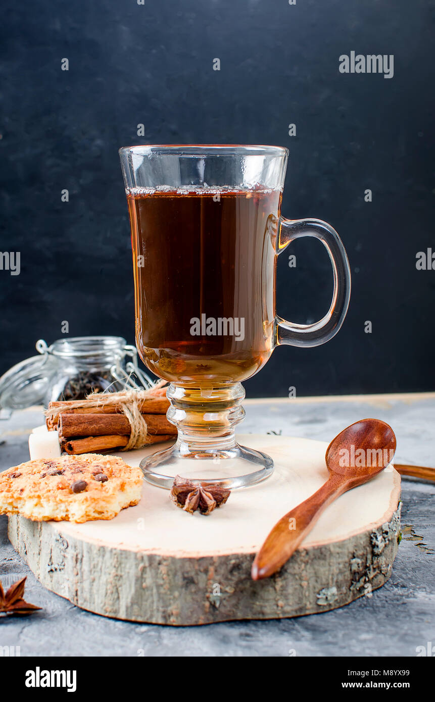 Black tea in cup on dark  background, Cup of tea, biscuits, spices for tea. - Stock Image