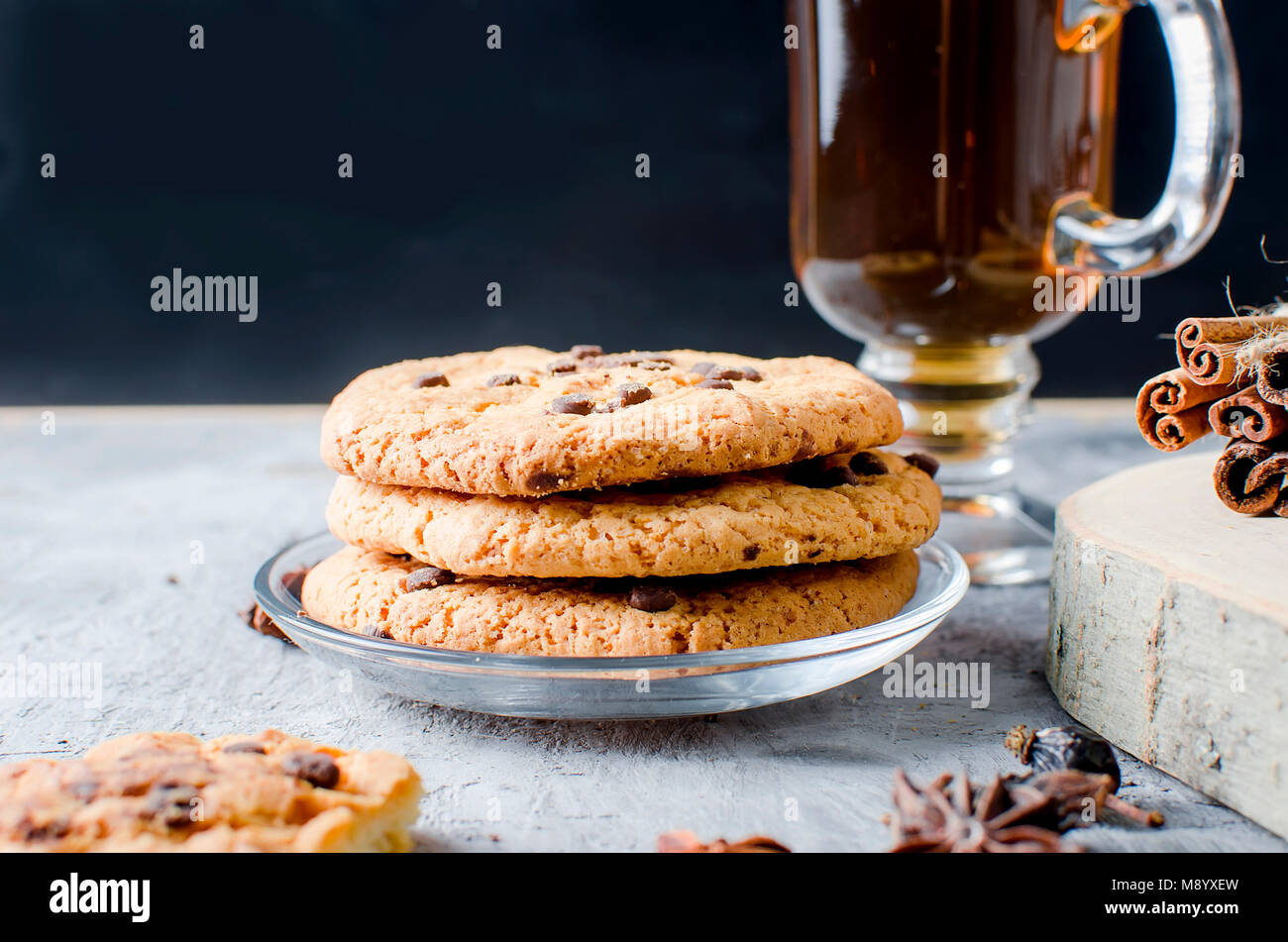 stack of homemade cookies with chocolate drops, сup of hot black tea, cinnamon, anise on dark   background, spices - Stock Image
