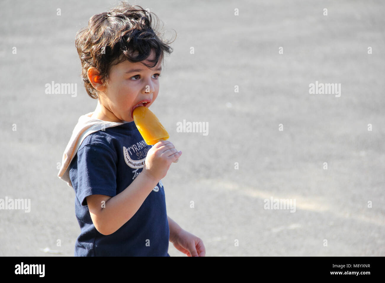 London, UK - July 09, 2017 - Little boy eating ice lolly at South Bank in hot weather - Stock Image