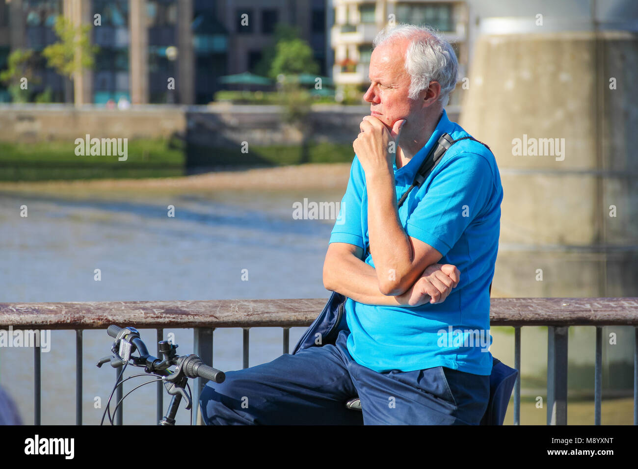 London, UK - July 09, 2017 - A grey-haired man looking over the riverside at South Bank in a hot weather - Stock Image