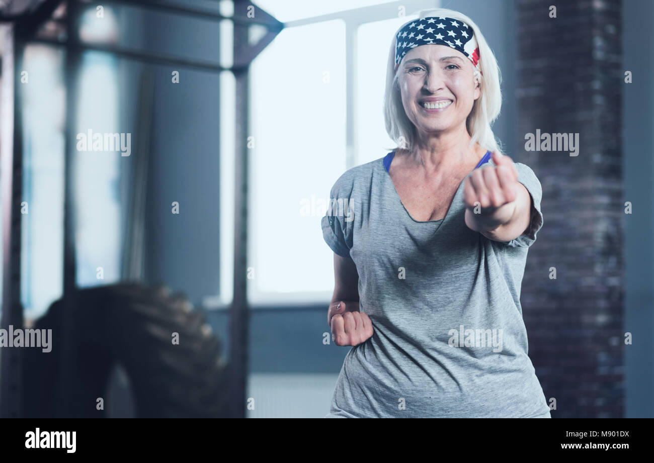 Radiant woman looking into camera while taking exercise class - Stock Image