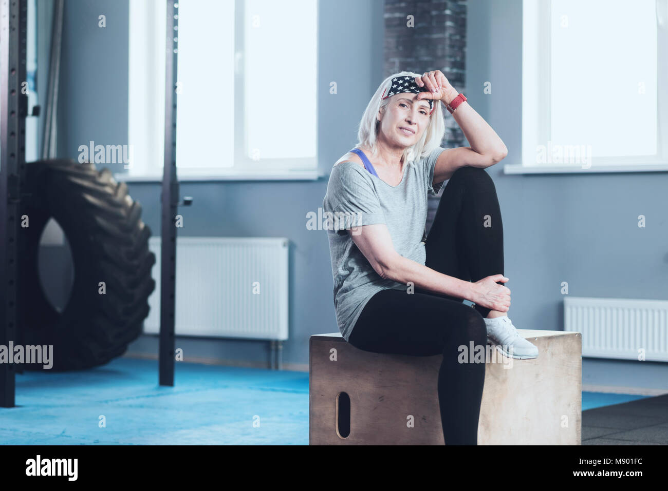 Pretty mature woman smiling while resting at gym Stock Photo