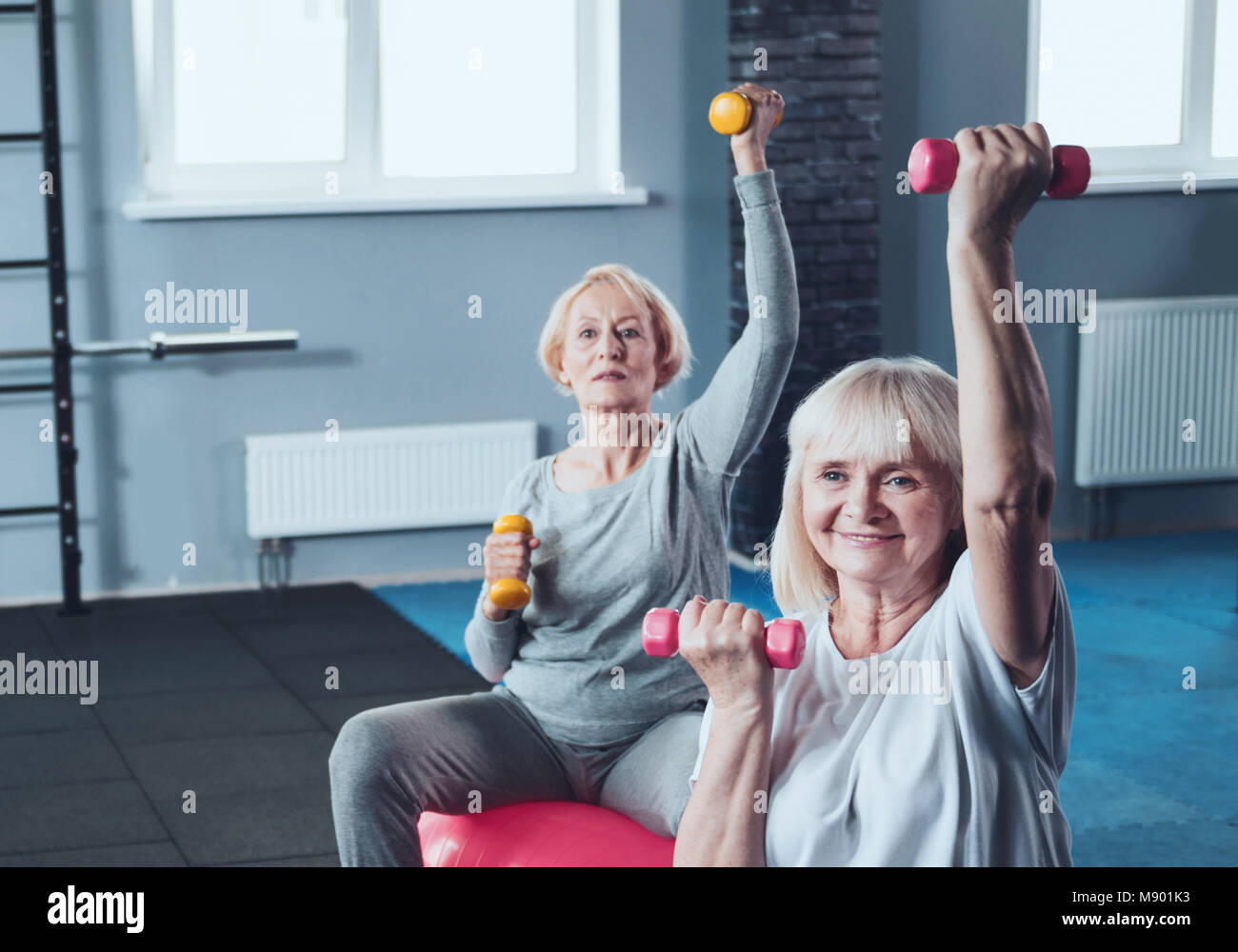 Sporty retired women doing exercises with dumbbells at fitness club - Stock Image
