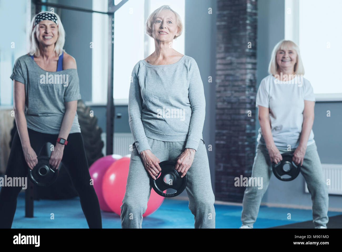 Active mature women swinging weight disk at gym - Stock Image